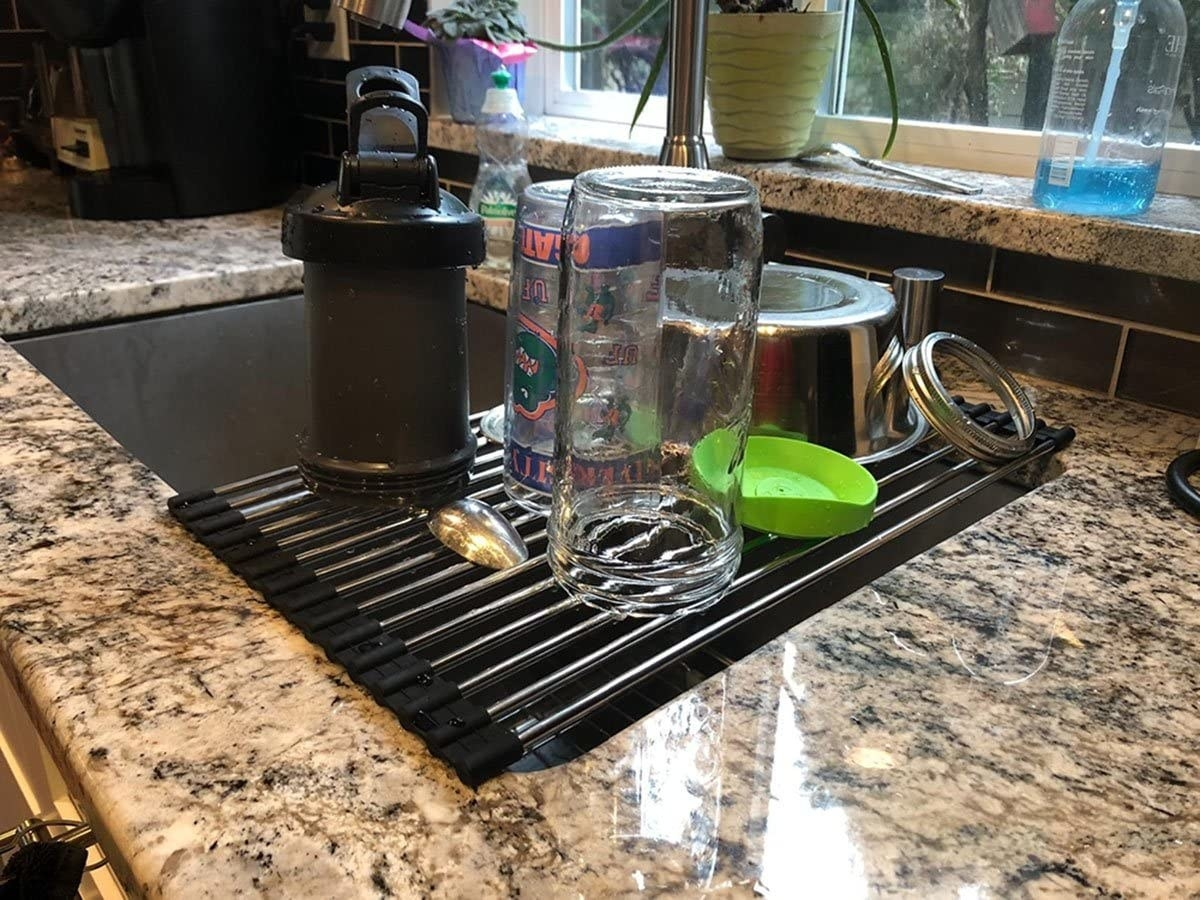 The drying rack unrolled over the sink, holding clean dishes