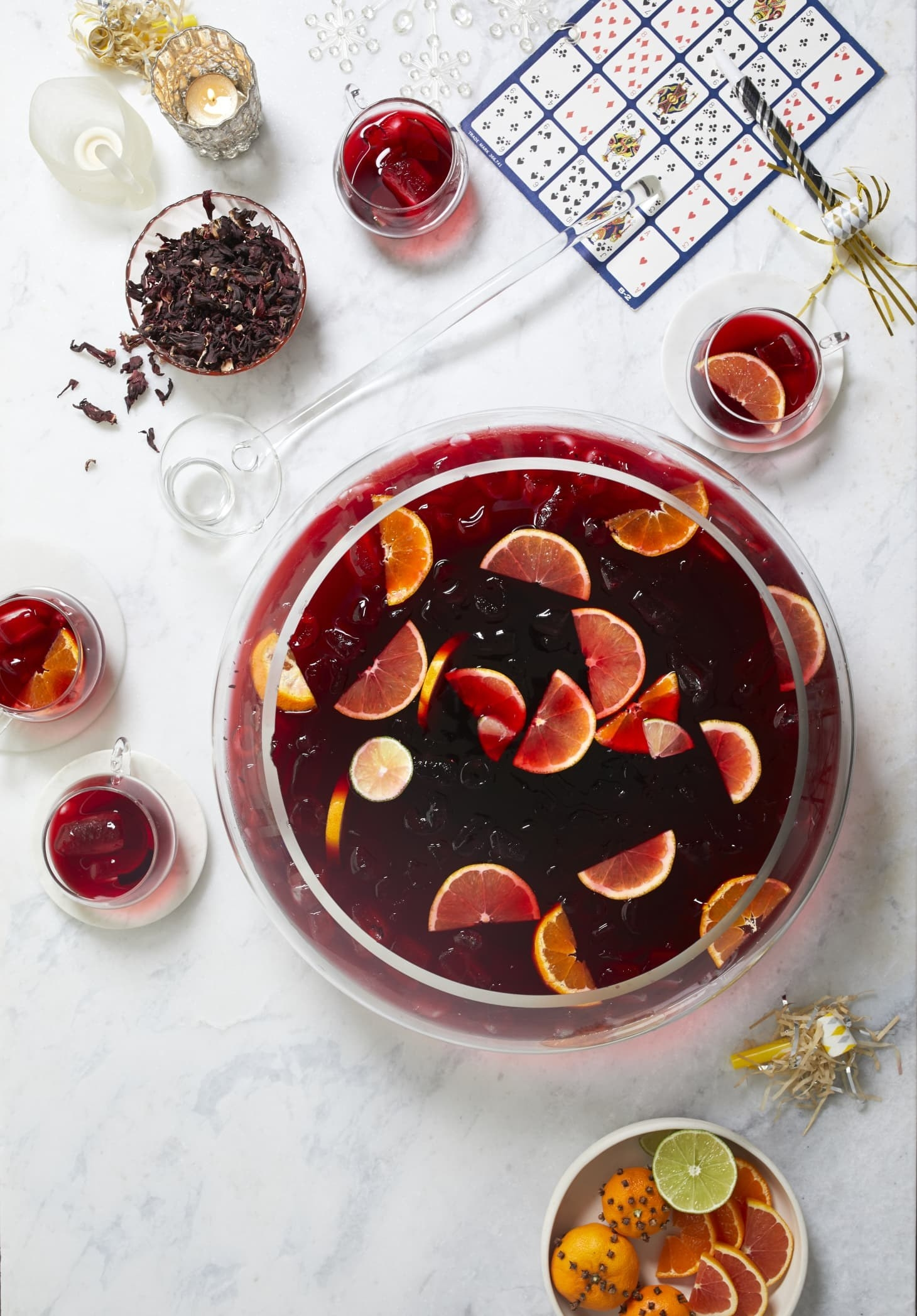 A large bowl filled with Jamaican Sorrel Punch garnished with citrus slices.