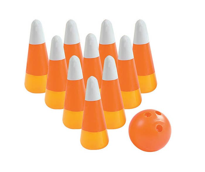 bowling pins that look like candy corn and an orange bowling ball