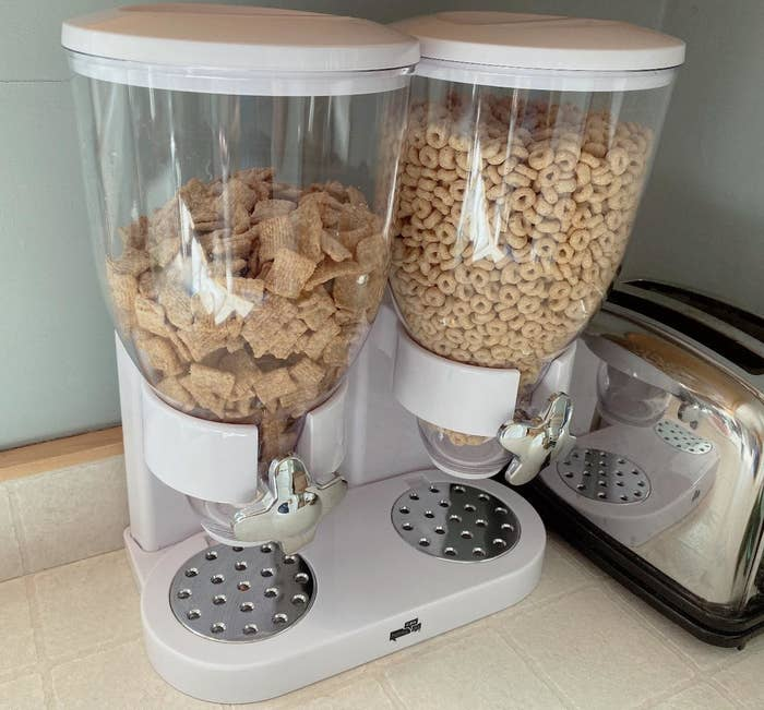 reviewer's white and clear cereal dispenser with silver knobs on their kitchen counter
