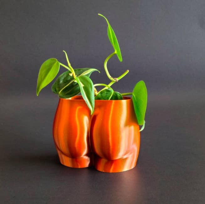 3D-printed copper booty-shaped pot with green plant inside