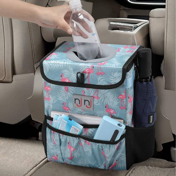 cube-shape car trash can in a flamingo print with storage pockets on the front and sides