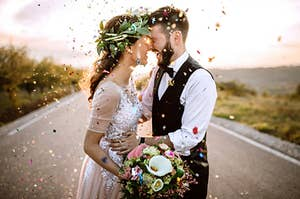 A man and woman in their wedding outfits surrounded by colorful confetti