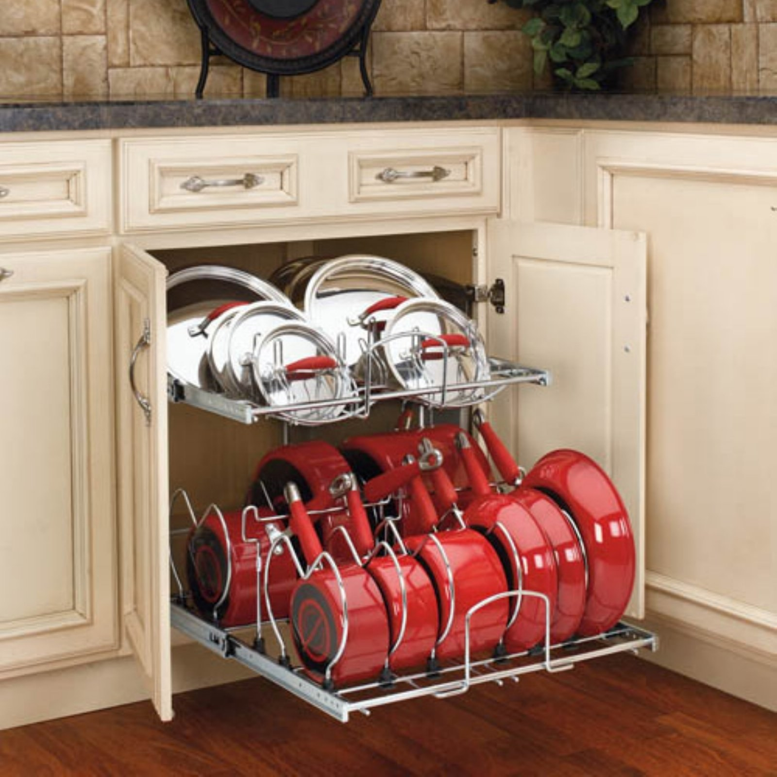 Red pots, pans, and metal tops organized in the kitchen cabinet