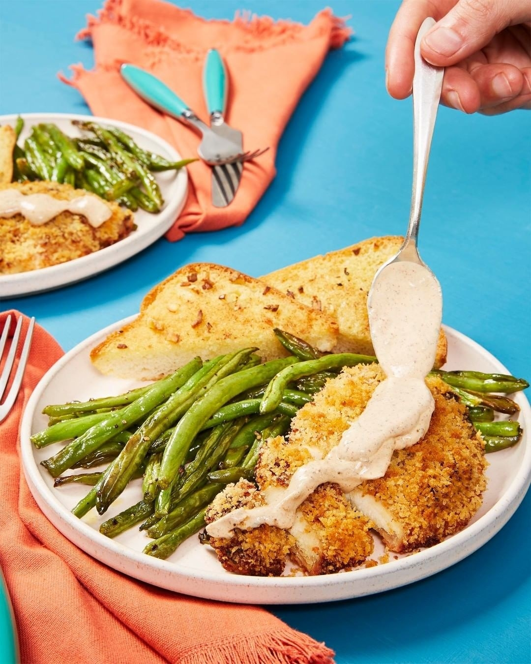 A plate of breaded chicken, green beans, and toast