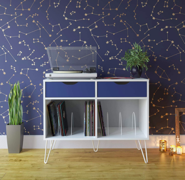 Navy blue and white turntable stand with record player on top, two navy blue drawers, and two vinyl shelves on the bottom against a constellation-print wall.