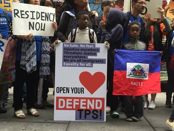 """Children hold a Haiti flag and a sign that says """"Open your heart, defend TPS"""""""