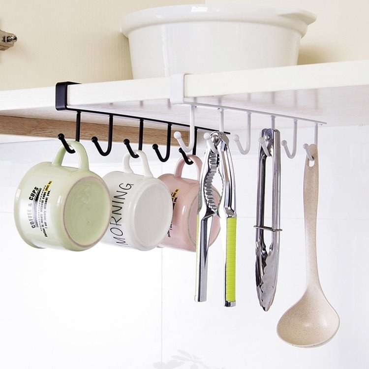 Mugs and kitchen utensils hanging on hooks