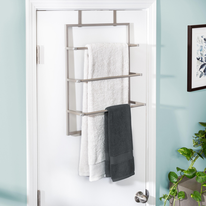 Metal towel rack hanging behind a door
