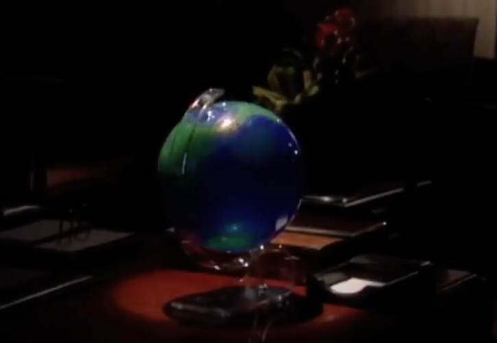 A screenshot of a globe sitting on a desk in a dark room