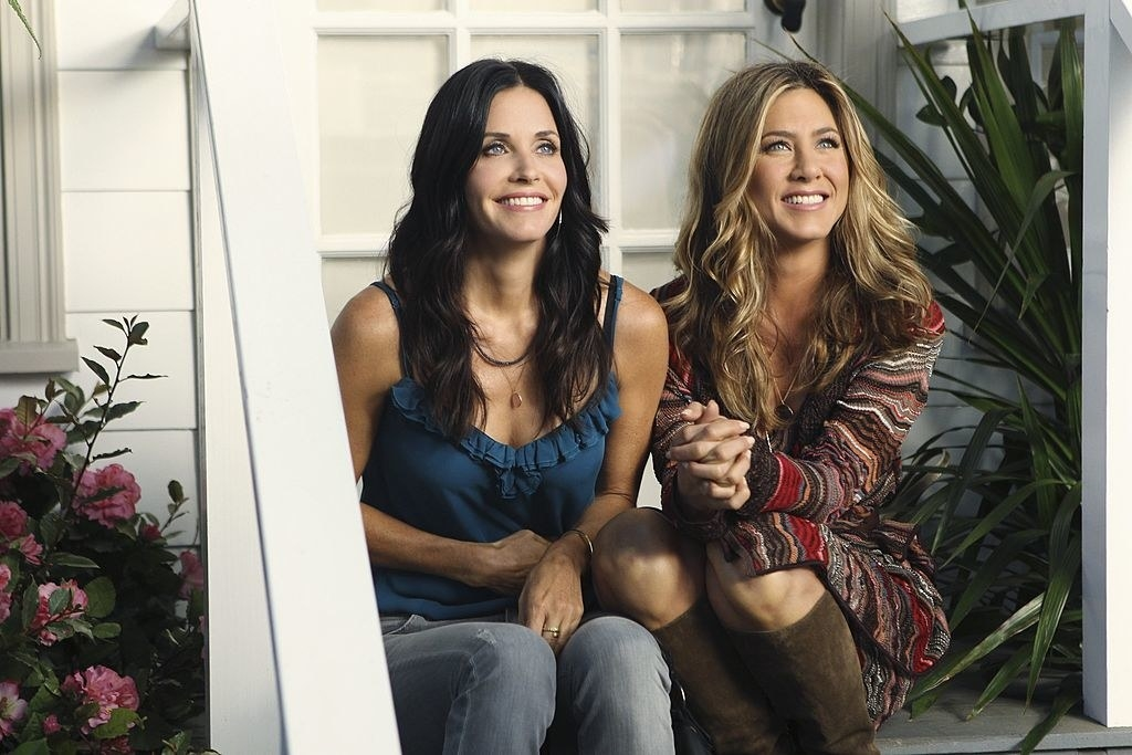 A promotional photo of Courteney Cox and Jennifer Aniston sitting on outside staircase