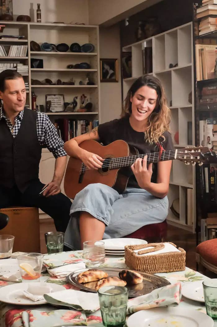 a woman smiles and sings as she plays a guitar and a man looks on appreciatively