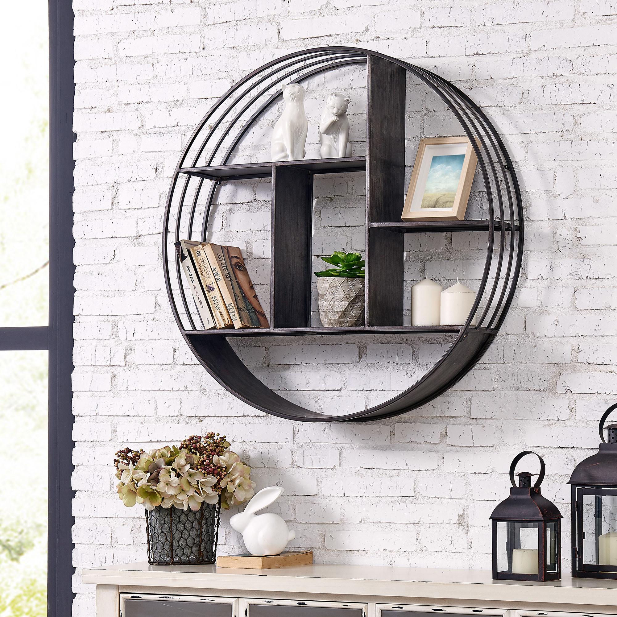 A metallic gray circle shelf on a white brick wall