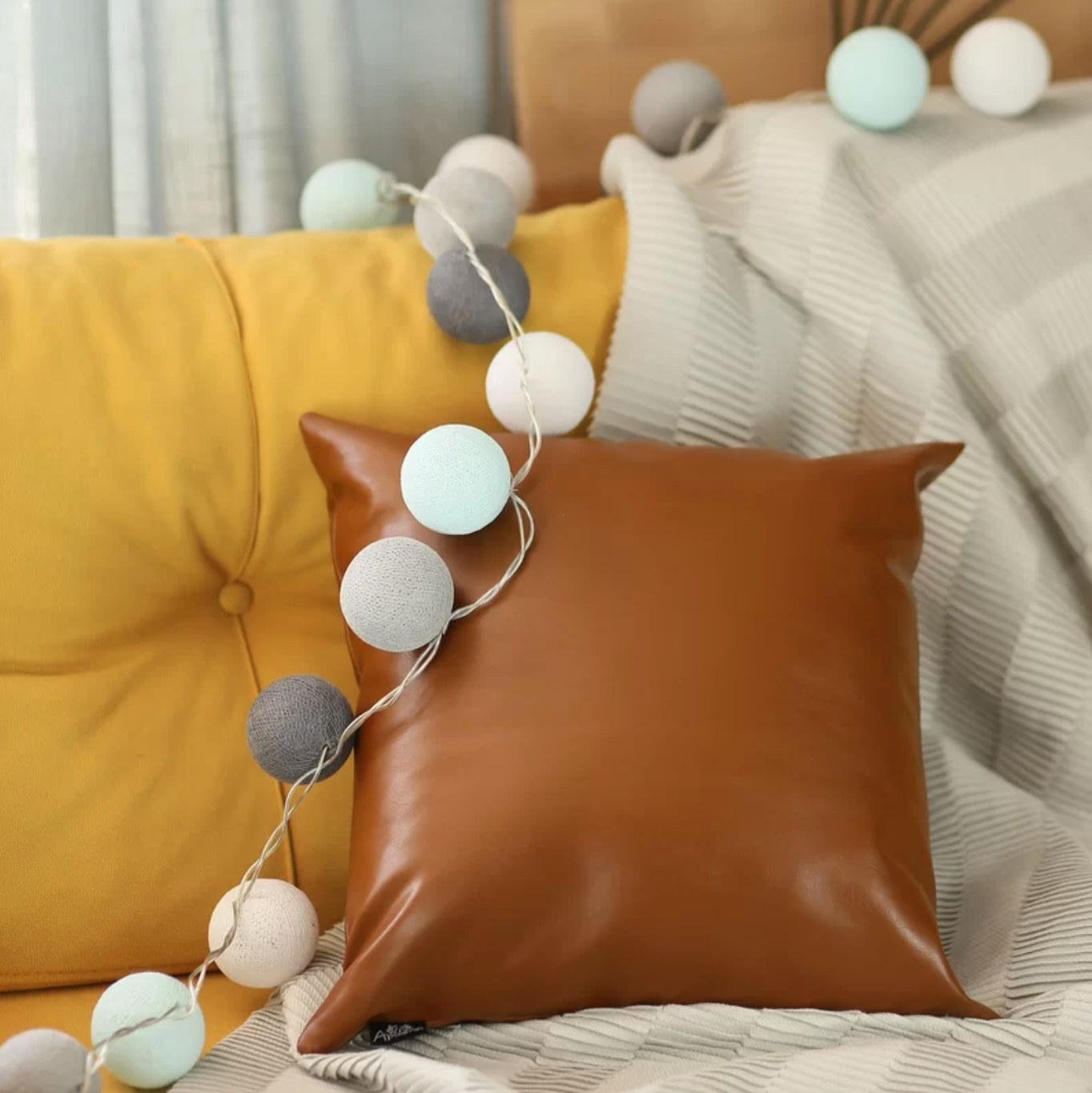 The brown pillow on a couch with string lights draped across it