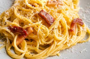 A pile of creamy spaghetti carbonara studded with crispy pancetta, black pepper, and shredded cheese
