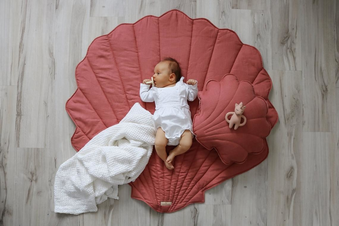 Baby dressed in white laying in center of mat