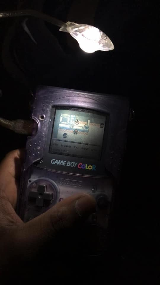 A Gameboy with a flashlight illuminating the screen