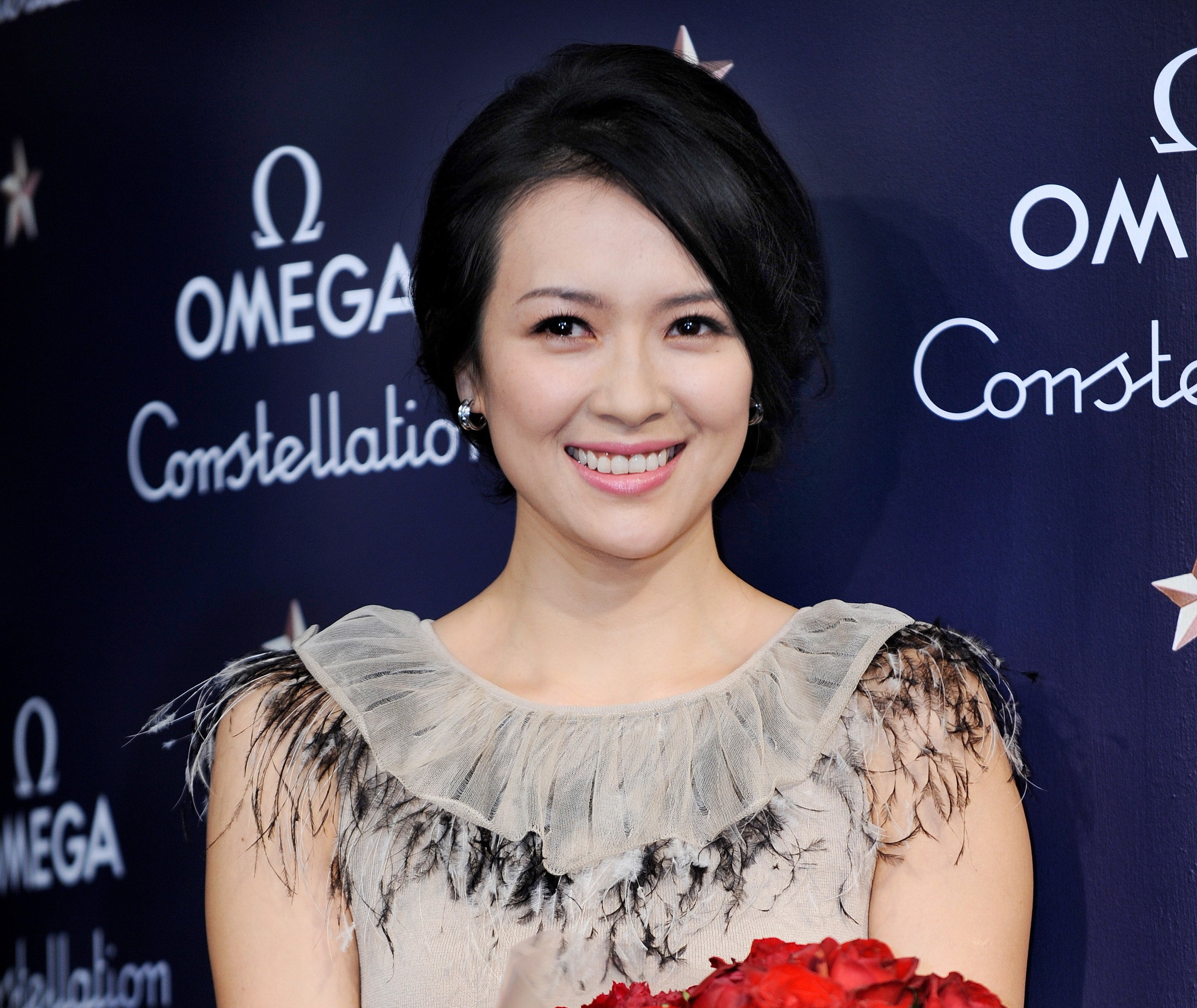 Zhang Ziyi smiling at a event in Tokyo as she holds a bouquet of red roses