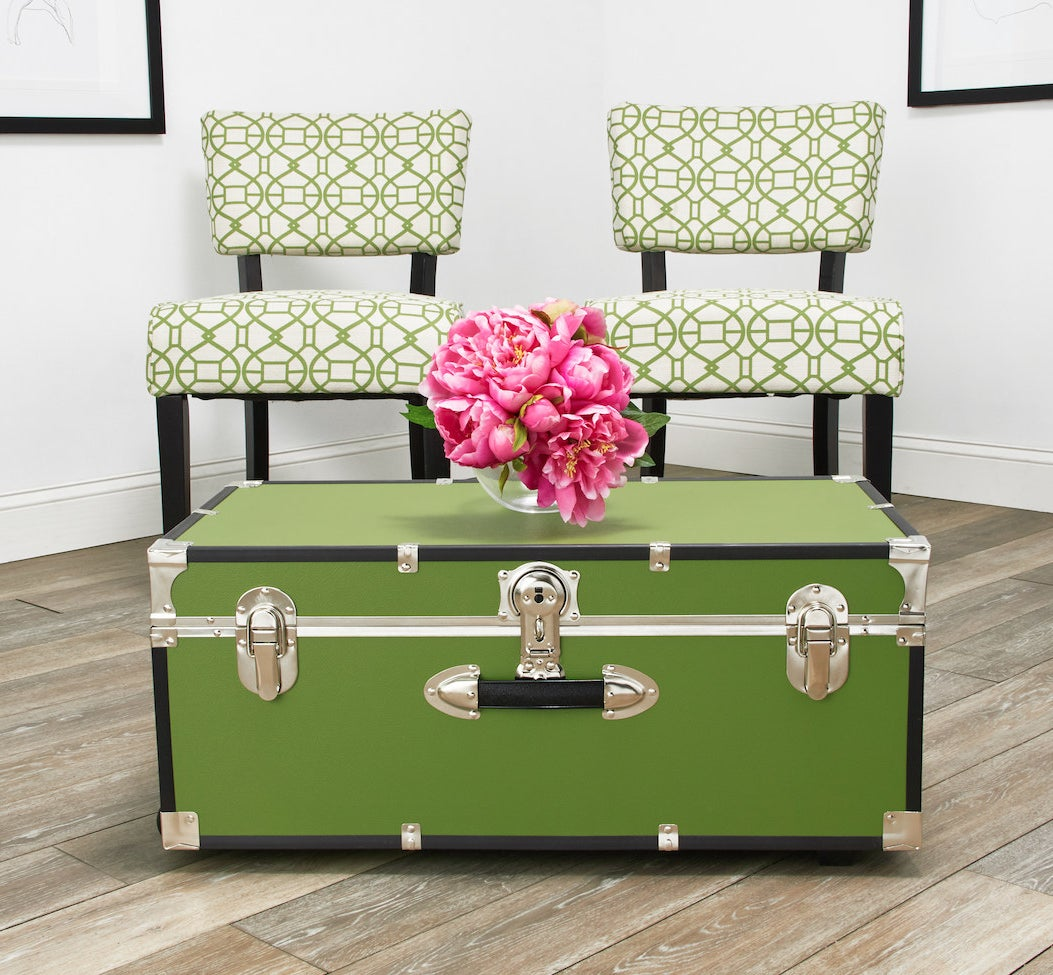 The green trunk in front of green patterned chairs
