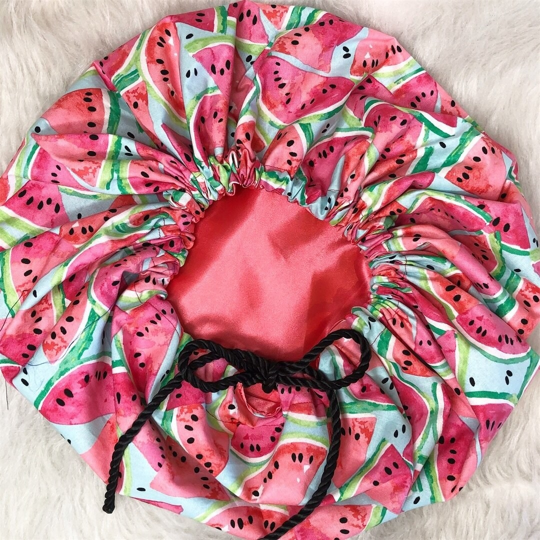 A watermelon-print bonnet with a cotton cover and pink satin lining