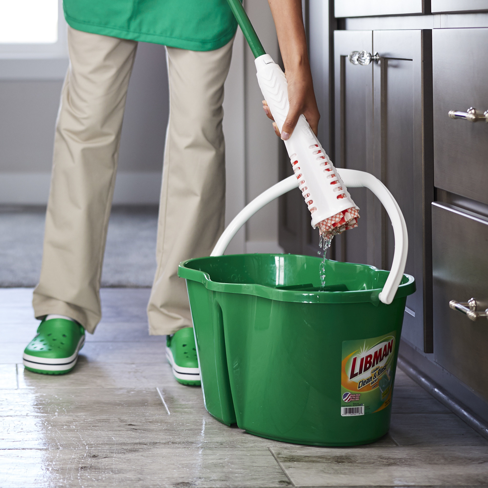 A model using the built-in wringer to remove some of the water from a microfiber mop