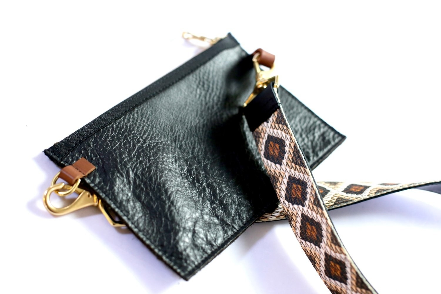 Black leather rectangular clutch with brown leather and gold clasp details and an added strap