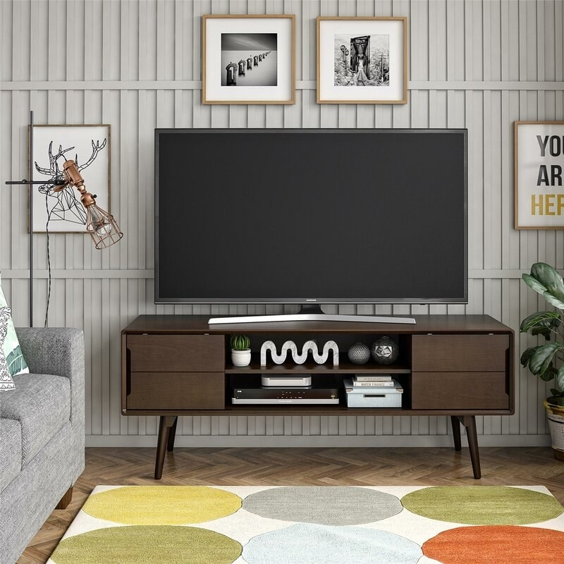 Dark brown wood tv stand with peg legs and two shelves and two doors on either side with a tv sitting on top of it.
