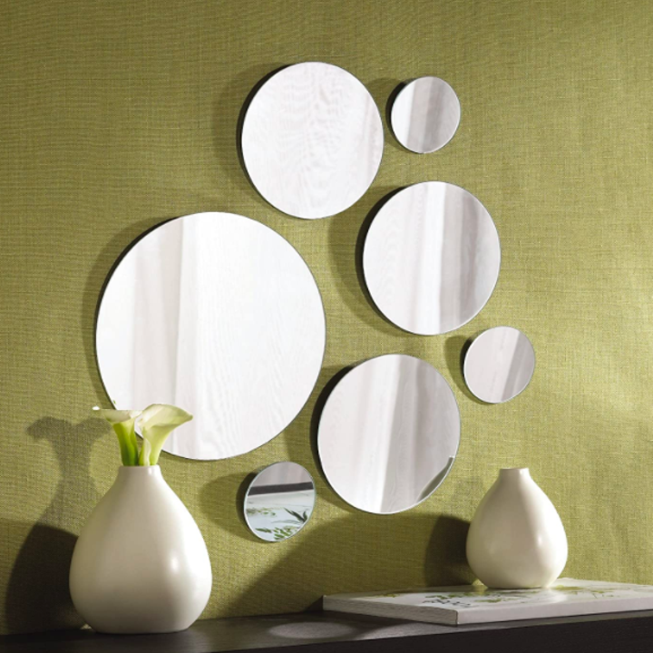 Set of seven big and small circle-shaped mirrors hanging on a green wall above a table