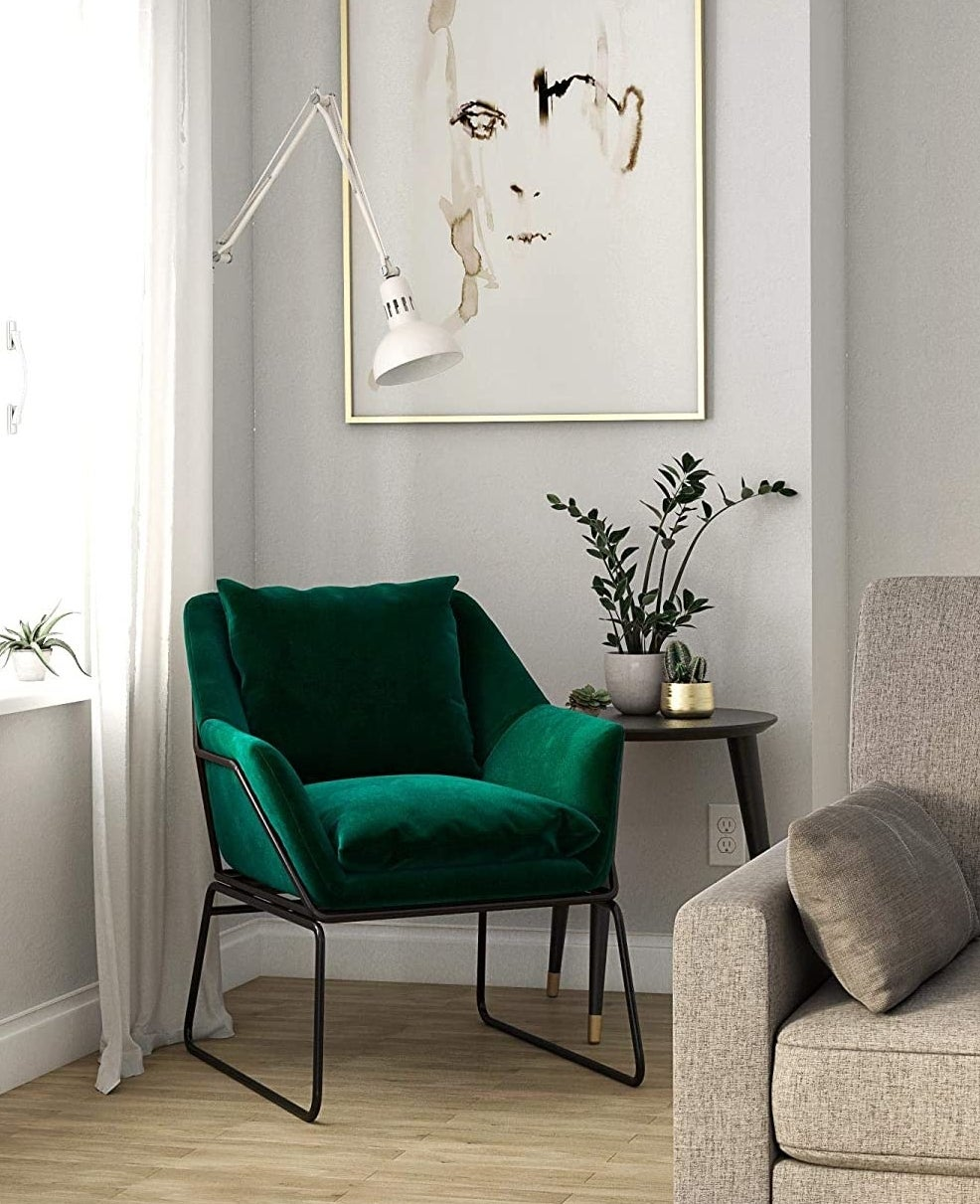 Green velvet chair with back pillow and black metal frame in a living room.