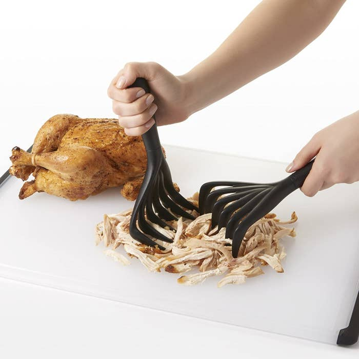 model's hands shredding chicken with the shredders which look a lot like thick plastic rakes for food