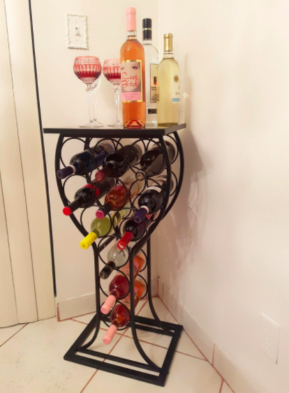 Reviewer's black wine-shaped wine rack with bottles of red and white wine in a corner