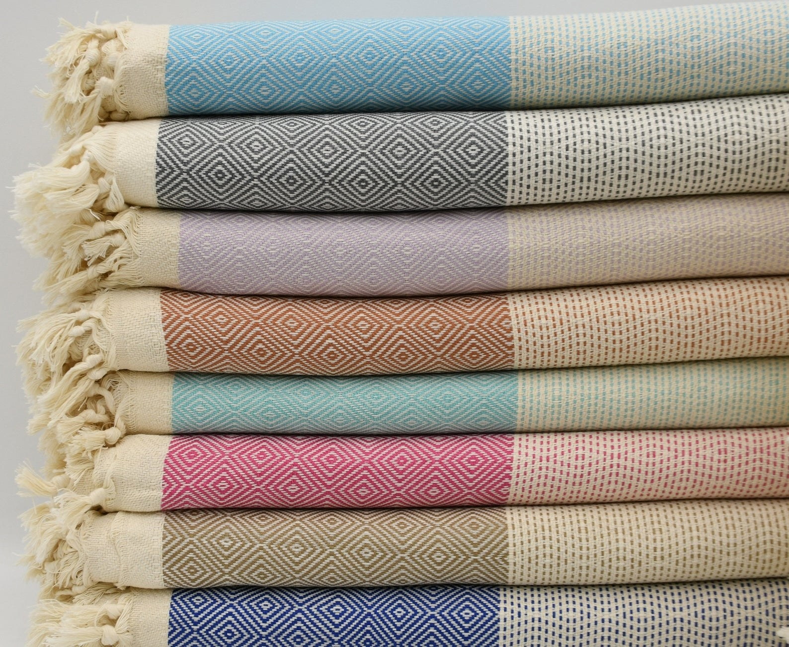 a stack of patterned blankets in different colors with fringed edges