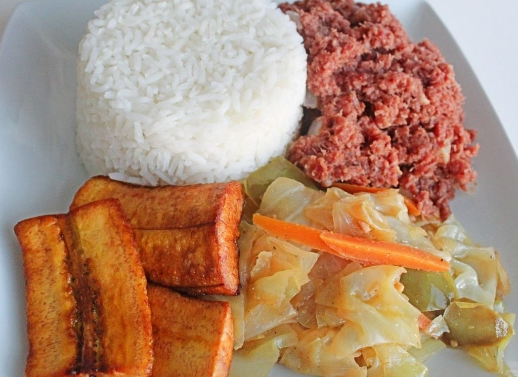 A plate of Jamaican steamed cabbage, fried plantains and white rice.