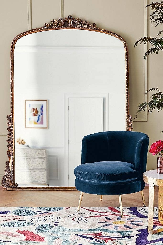 Wide floor-length mirror with a rounded top and gold frame with jeweled adornments on the top middle and bottom side edges.