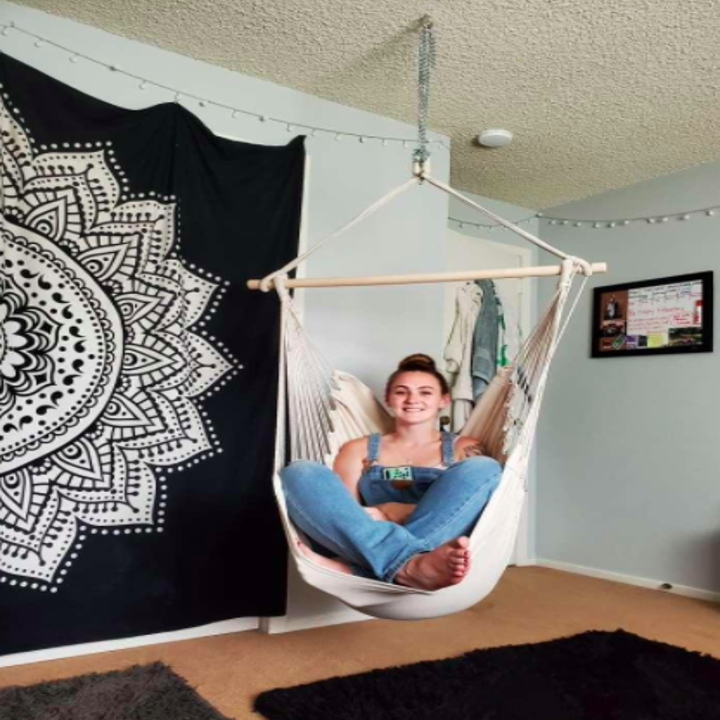 Reviewer lounges in white hammock chair in front of a black and white wall tapestry