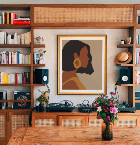 Framed art print of African American woman wearing gold hoops and a yellow dress on a wall about a wooden bookcase and DJ equipment