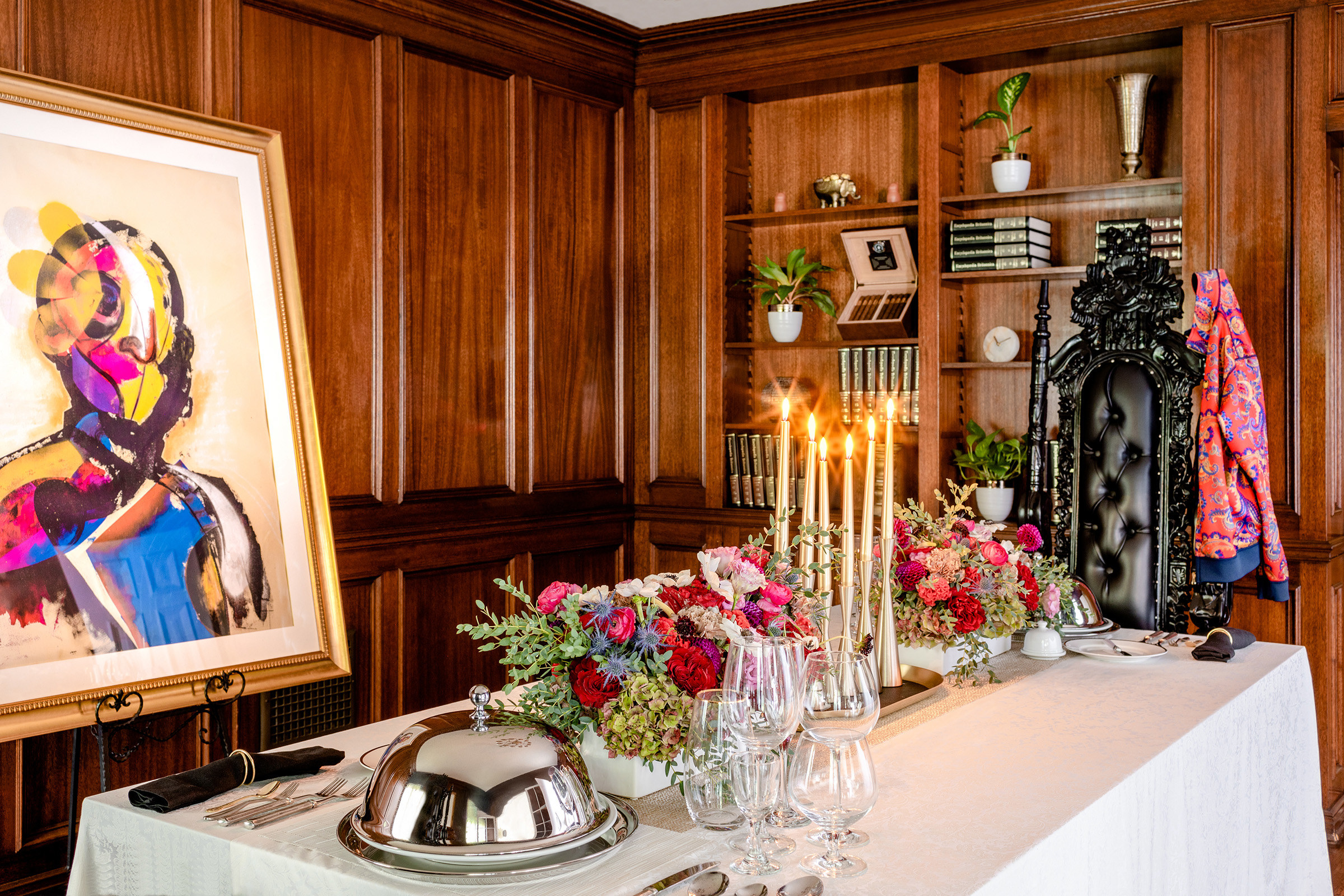 A tableclothed table topped with flowers, crystal glass, candles, and covered silver platters with an ornate, tall black chair at the head