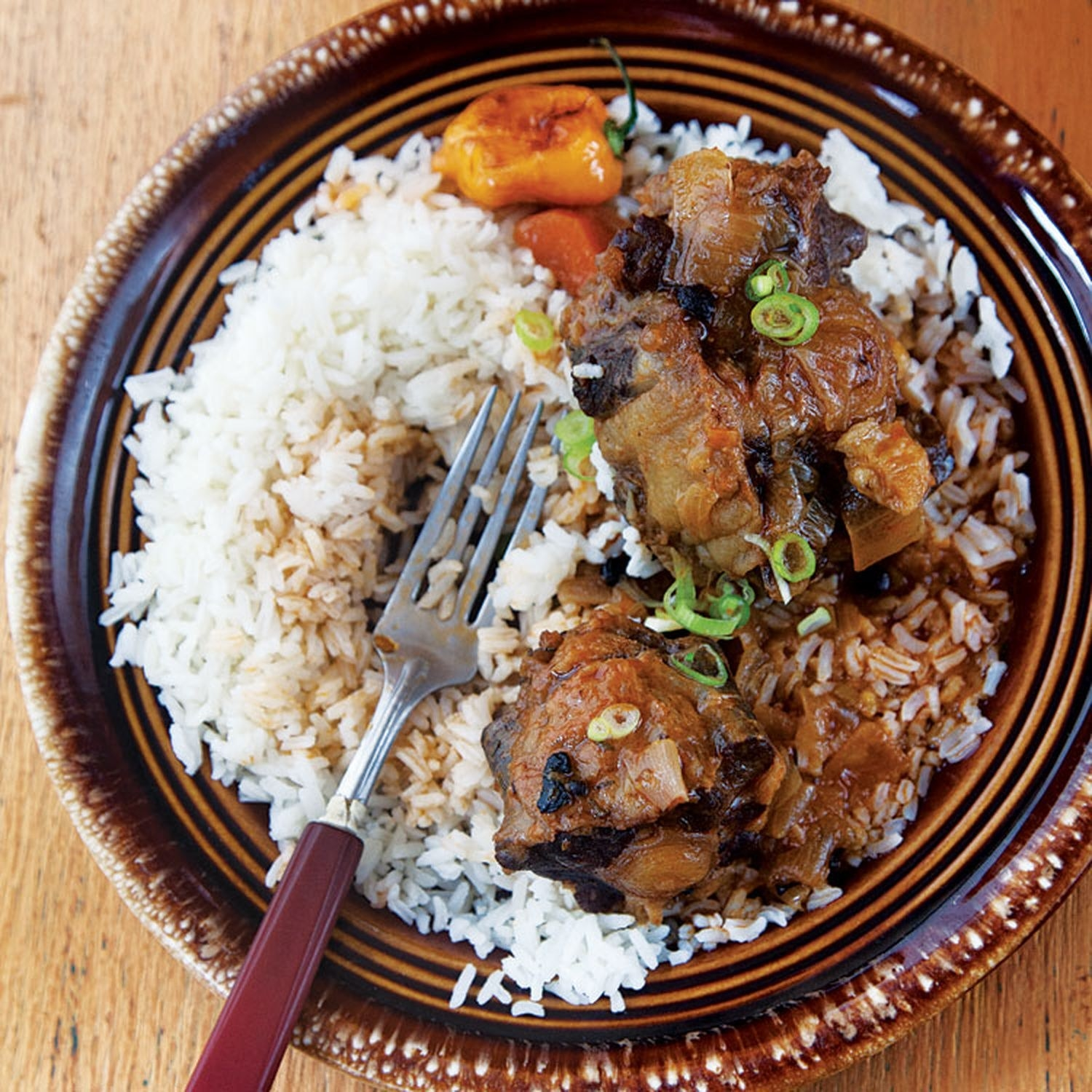A plate of oxtail stew with a side of white rice, garnished with fresh scallions.