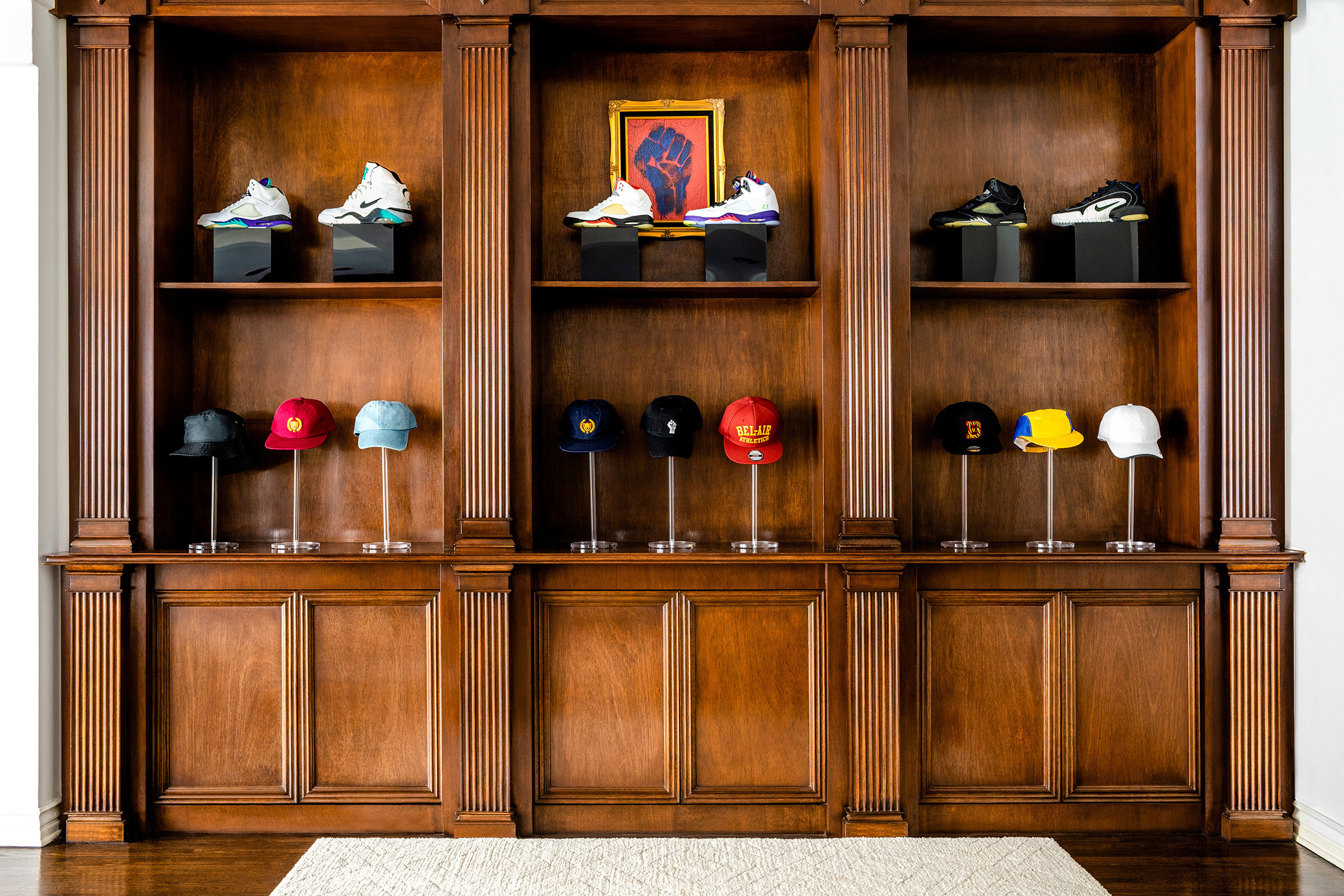 Dark wooden ornate shelving holds fancy sneakers and hats on pedestals