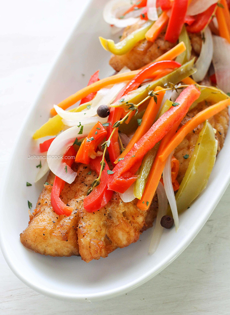 A plate of fried snapper topped with thinly sliced bell peppers and onions.