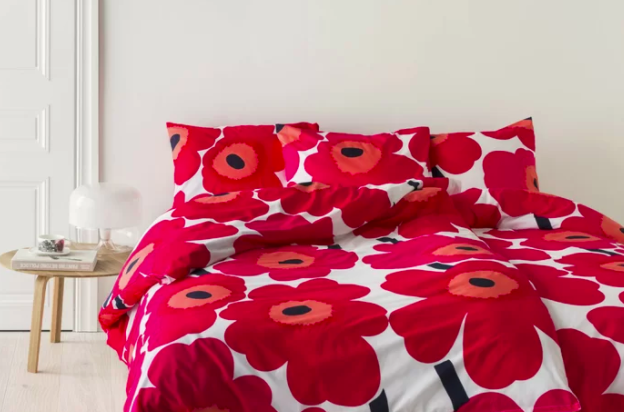 Abstract red flower reversible comforter and pillow shams on a low full-sized bed