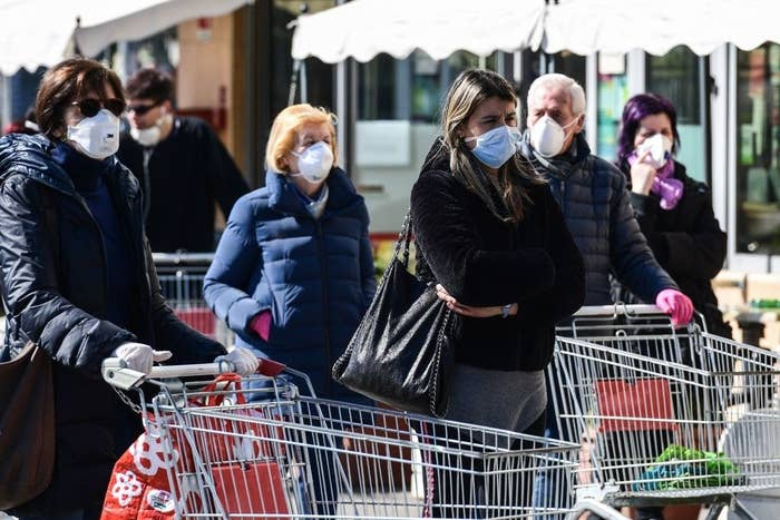 People waiting outside a grocery store with face masks on