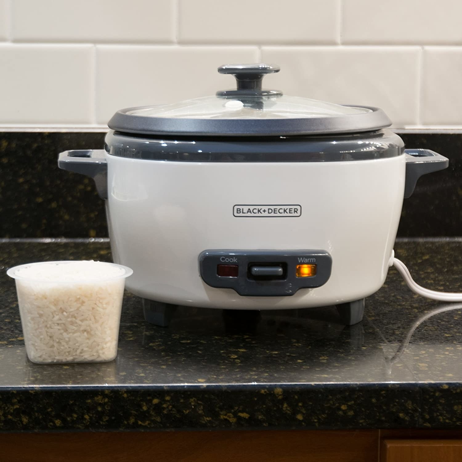 A plugged in rice cooker beside a cup of rice