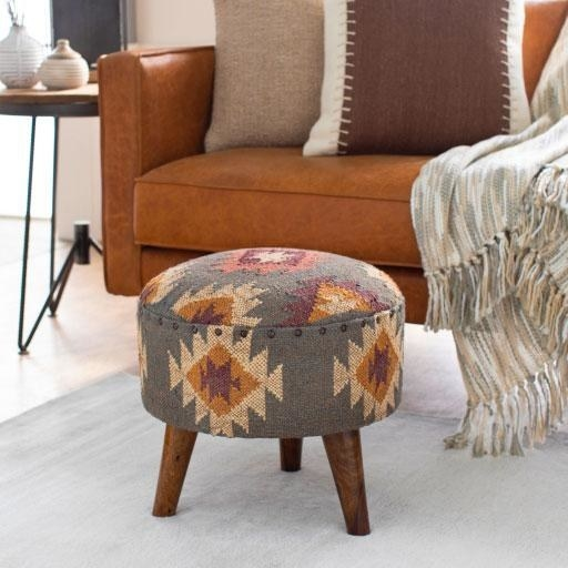 The circular stool in grey with wood legs and a orange, red, and tan triangle and diamond pattern all over it.