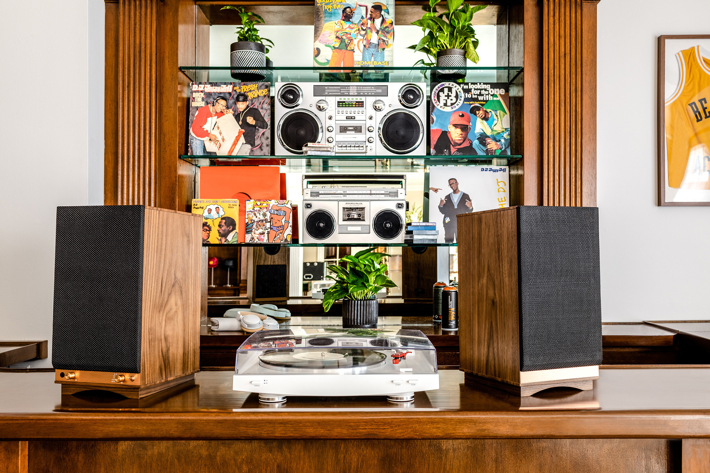 A dark wooden table holds a record player and speakers with shelving of stereos and vinyls behind it