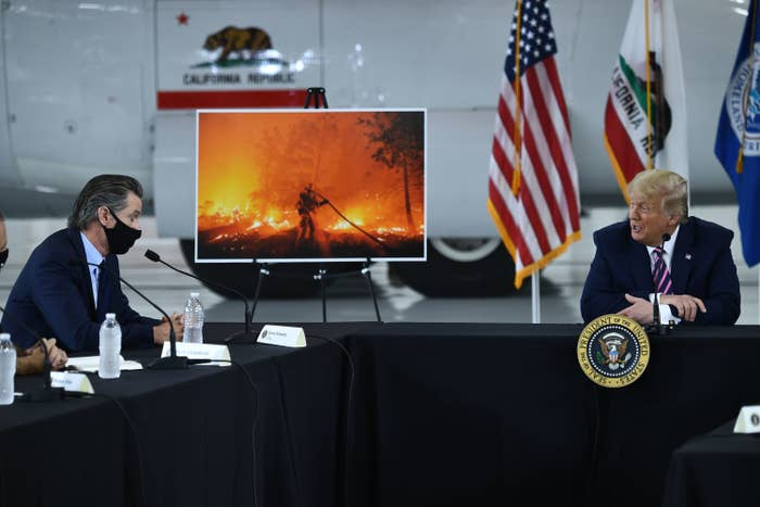 Donald Trump, not wearing a mask, sits at an L-shaped table and speaks with Gavin Newsom, who is wearing a black face mask