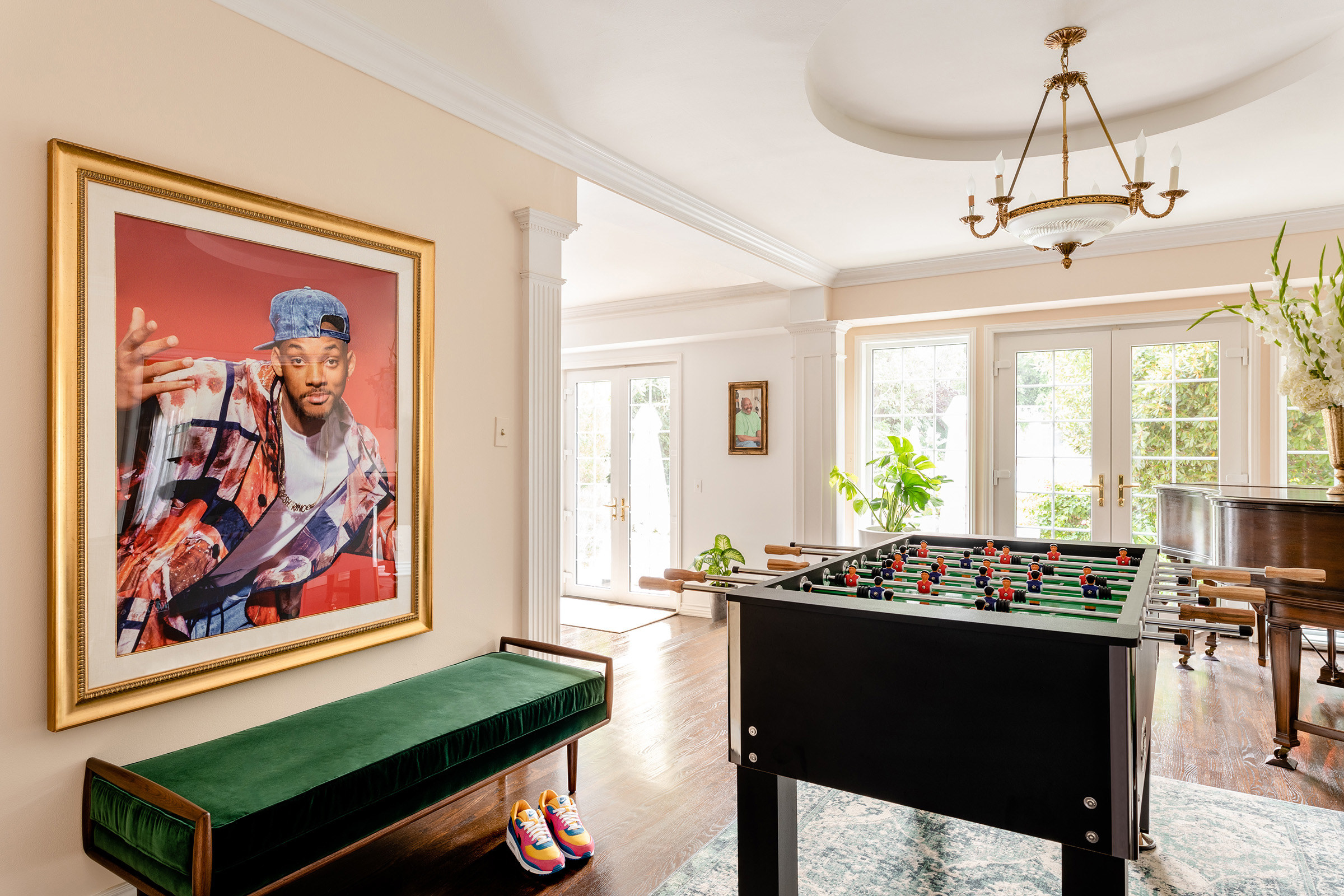 A room filled with a foosball table, piano, and a framed photo of Will Smith (à la Fresh Prince) on the wall