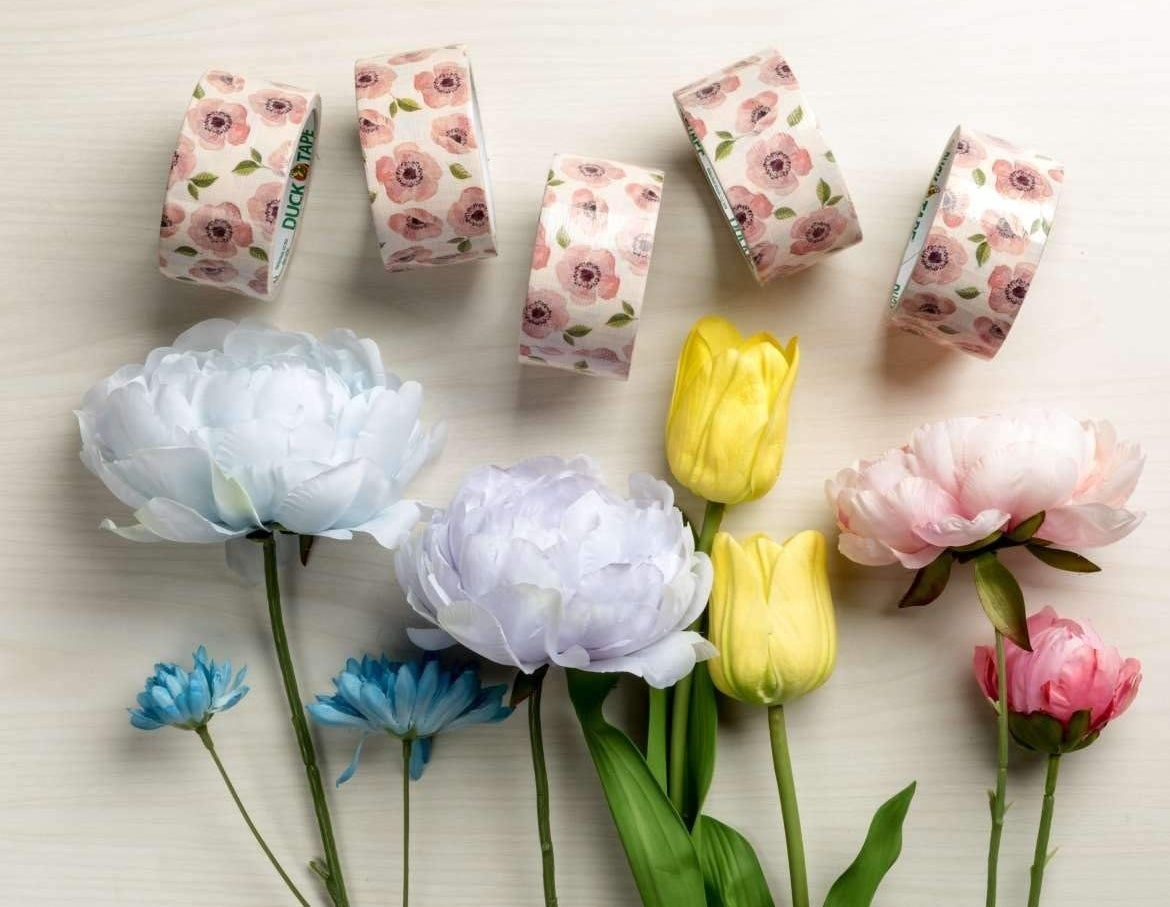A set of duct tape with flower prints on a background with real flowers as decoration