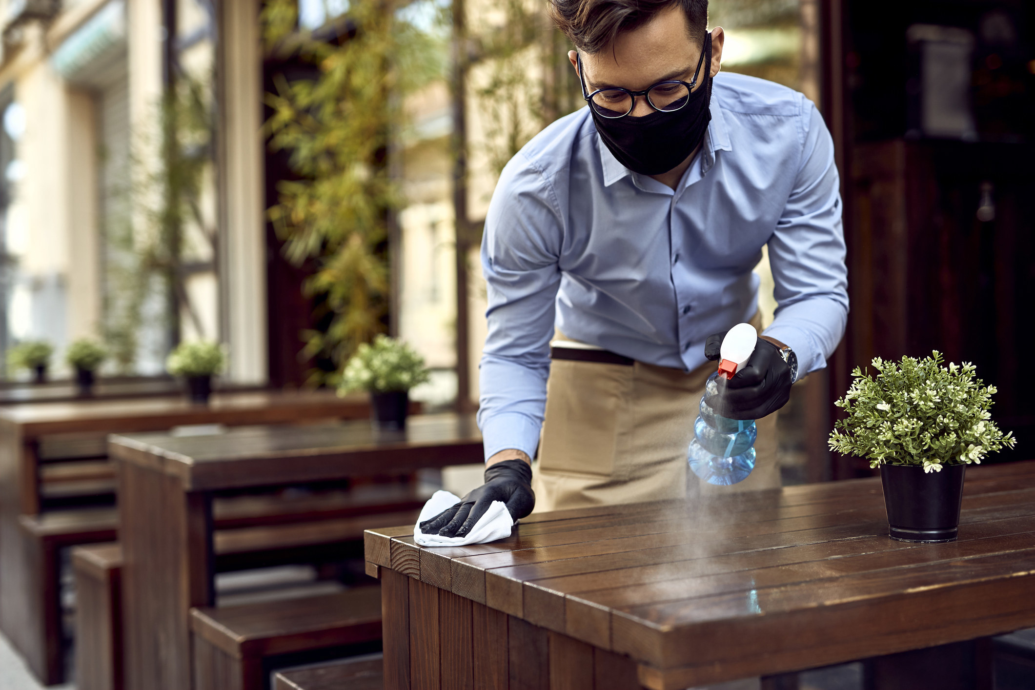 A waiter wiping down an outdoor table