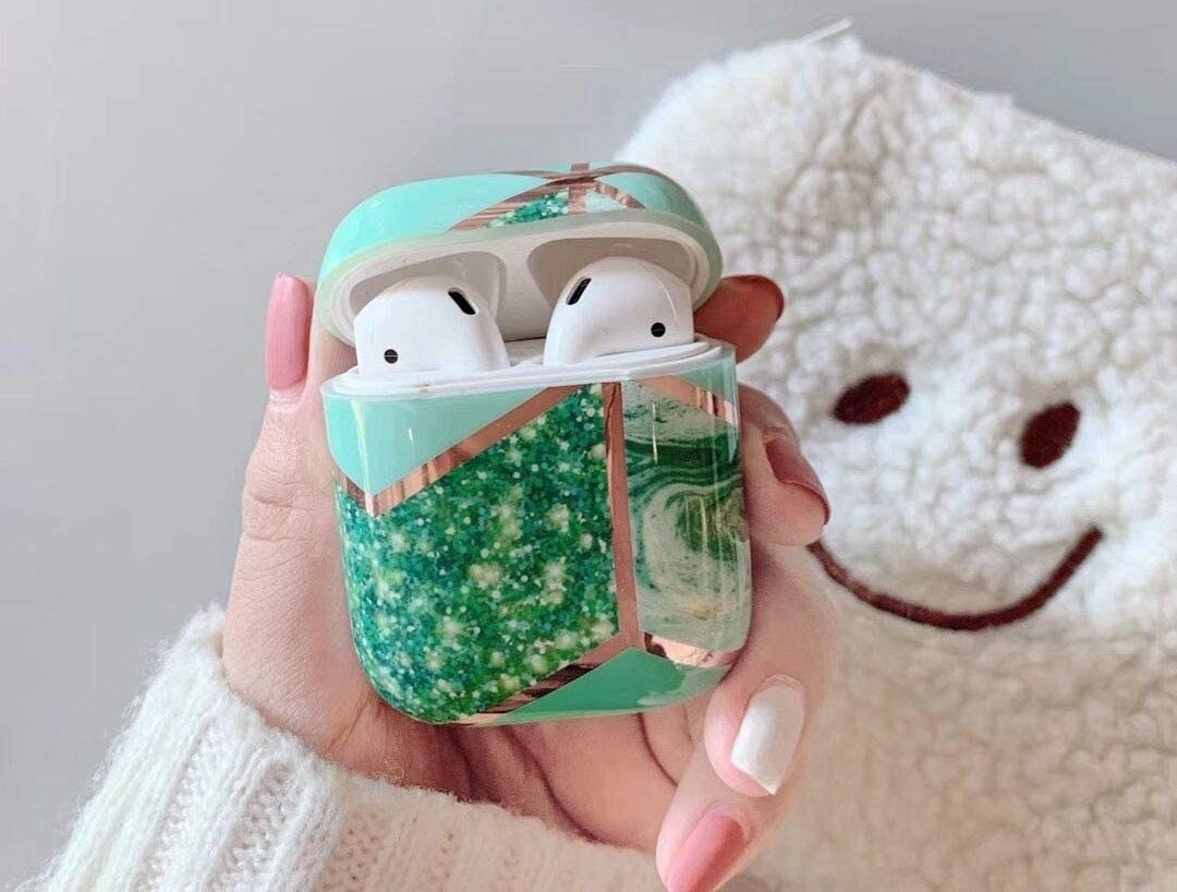 A hand holds a case with AirPods in it that has marble patterns and gold foil accents